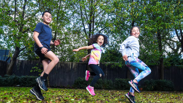 Alex, Hattie and Georgie Curvich doing their regular backyard exercises. Georgie misses sports and is training for cross country by running with her dad.