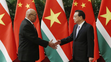 Suriname's President Desi Bouterse shakes hands with Chinese Premier Li Keqiang before a meeting at the Great Hall of the People this week.
