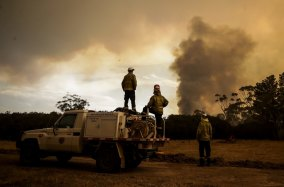 Fire crews work to defend resident Les Hart's property as the North Black Range bushfire approaches, seen near Bombay, NSW, on November 29, 2019.