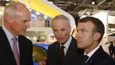 French President Emmanuel Macron, right, listens to Jean-Dominique Senard, centre, Michelin CEO, at the Paris auto show on Wednesday.