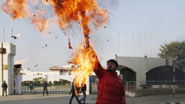 A Nepalese protester burns an effigy of Prime Minister Khadga Prasad Oli in front of the parliament building in Kathmandu on Sunday.