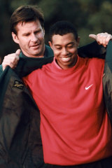 Nick Faldo presents Tiger Woods with his first green jacket in 1997.