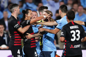 Daniel Georgievski clashes with Sydney FC players during a controversial end to the last derby two weeks ago.