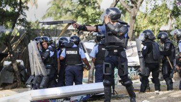 A Nicaraguan police officer aims his weapon at protesting students on Friday.