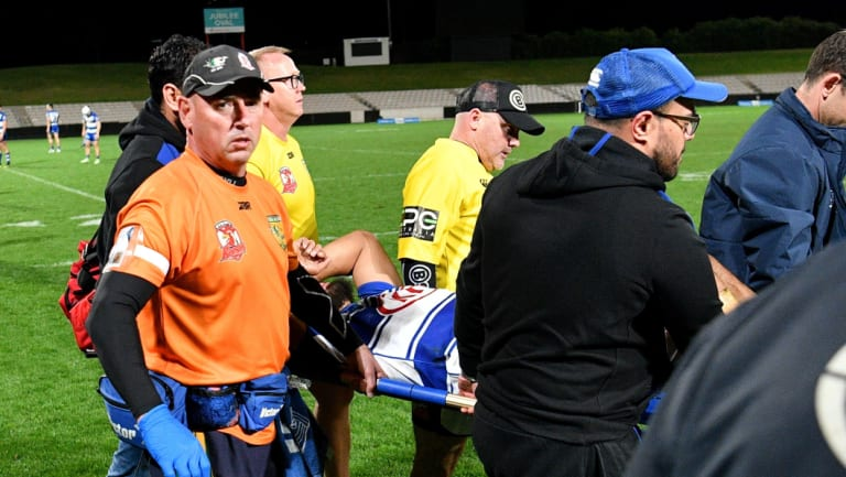 Down and out: Fine is carried off after suffering a serious injury late in the season.