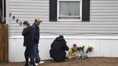 Mourners organize a memorial outside a mobile home in Colorado Springs, Colorado.