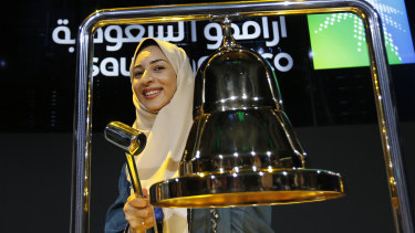 Aramco employee Sukaynah Al Oqaili ringing the stock bell on Riyadh's stock market during the official trading debut ceremony.