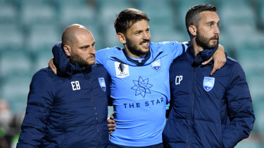 Milos Ninkovic is helped off the field after hurting his ankle in Sydney's FFA Cup defeat to Brisbane at Leichhardt Oval.