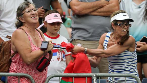 Two fans fight over Aryna Sabalenka's black headband.