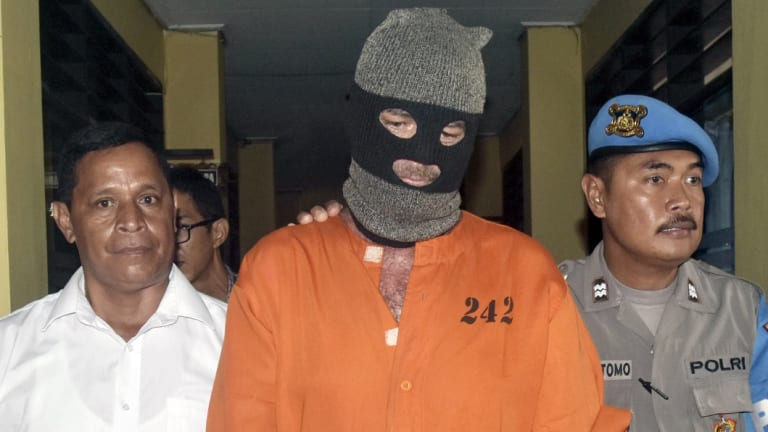 Police officers escort Brendon Luke Johnsson through police headquarters at Denpasar, Bali.