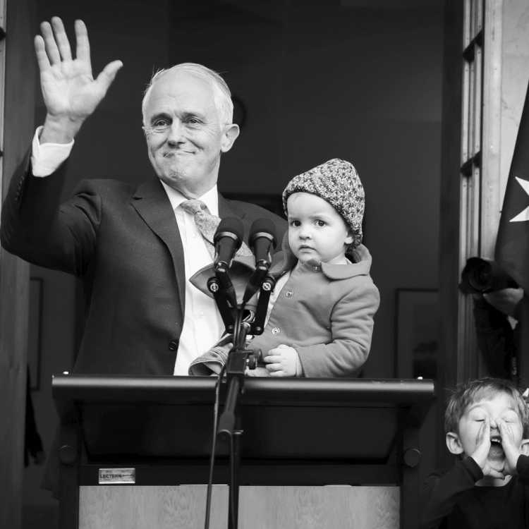Malcolm Turnbull, holding granddaughter Alice, waves goodbye as grandson Jack plays with the media.