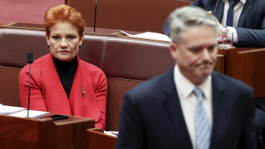 Minister for Finance Mathias Cormann walks back to his seat after speaking with Senator Pauline Hanson in June.