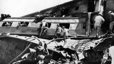 Rescue workers clamber over the remains of the train in their frenzied search for survivors.