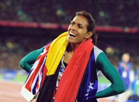 Cathy Freeman takes the Australian and Aboriginal flags on a victory lap after winning gold.