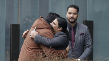 Abdul Aziz, center, a survivor of the Linwood mosque shootings, is embraced by friends outside the Christchurch District Court.