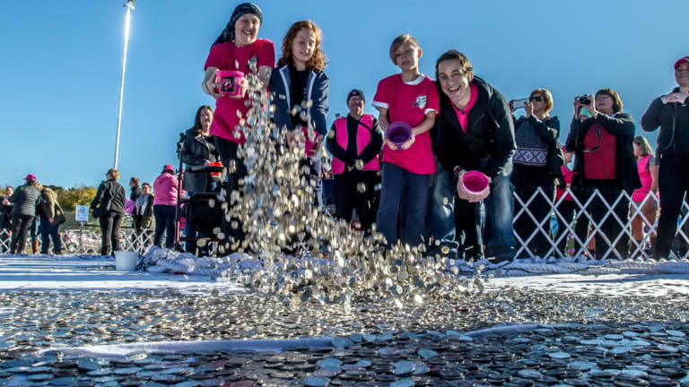 Connie, left, and her brother Samuel Johnson, right, and Connie's sons, Willoughby, 10, and Hamilton, 9, toss coins for their Big Heart Project, to raise money for cancer research.