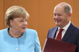 German Chancellor Angela Merkel of the Christian Democrats, and Finance Minister and Vice-Chancellor Olaf Scholz of the Social Democrats.