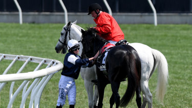 Jockey Ryan Moore is assisted by a race steward after The Cliffsofmoher was injured.