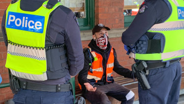 Police speak to a man at the Queen Victoria Market on Sunday.