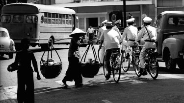 Police on bicycles patrol the streets of Saigon.