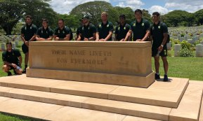 Reflective moment: Players pay their respects at Bomana War Cemetery.