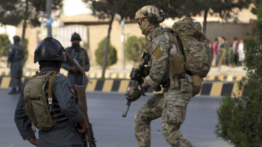 Afghan security personnel secure the site of an attack in Kabul that targeted the office of political offices of the President's election running mate.