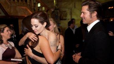 Angelina Jolie embraces Krystal Barter alongside Brad Pitt at the premiere of the film Unbroken in Sydney in 2014.