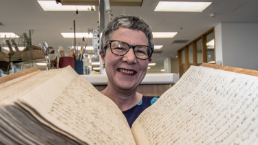 Director-General of the National Library of Australia, Dr Marie-Louise Ayres, pictured with the 250 year old captain's log from the Endeavour sailing.