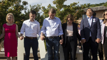 2020 Democratic presidential candidates hold hands as they stand together during a moment of silence to honour victims of recent mass shootings.