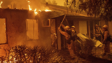 Firefighters work to keep flames from spreading through the Shadowbrook apartment complex as a wildfire burns through Paradise, California.