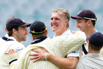 Will Sutherland is congratulated after taking a wicket.