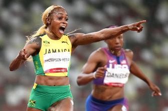 Elaine Thompson-Herah crosses the line and celebrates her gold medal.