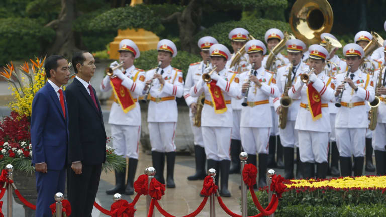 Indonesian President Joko Widodo, left, and Vietnamese President Tran Dai Quang on the podium during a welcome ceremony at the Presidential Palace in Hanoi on September 11.