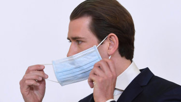Chancellor Sebastian Kurz adjusts his face mask as he announces Austria's lockdown measures will be eased.