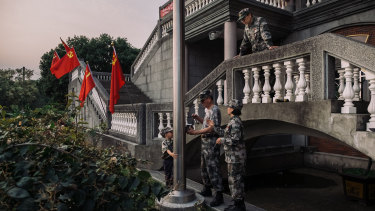 Wei Ming-jen adjusts a flagpole during a ceremony at the former Buddhist temple.