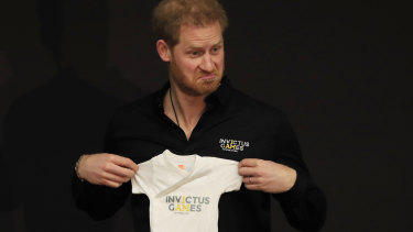 Prince Harry holds up an outfit for his newborn son presented by Princess Margriet of the Netherlands.