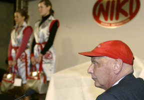 Former Formula One champion Niki Lauda, founder of the new Austrian discount airline Niki is seen during a press conference while stewardesses pose in their uniforms at Vienna's airport, March , 2004.