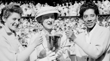 The Duchess of Kent, centre, presents the trophy for the Ladies' Doubles title to Angela Buxton, left, and Althea Gibson, right, following their victory at Wimbledon, England, 1956.