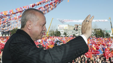 Turkey's President Recep Tayyip Erdogan salutes the supporters.