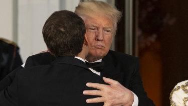 US President Donald Trump, right, greets Emmanuel Macron, on Tuesday.