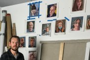 Artist James Needham in his Marrickville studio with some of the selfie portraits he has completed.