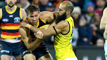 Clawed back: Tiger Bachar Houli stops Crows' Richard Douglas in his tracks during the round 13 match at the Adelaide Oval.