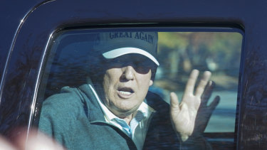 President Donald Trump waves to supporters as he departs after playing golf on Sunday.