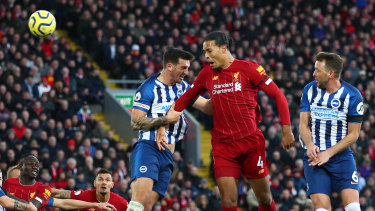 Virgil van Dijk of Liverpool climbs high to score his team's first goal against Brighton & Hove Albion at Anfield.