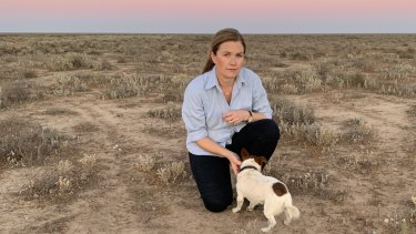 Alison McLean and her dog Gary in a paddock on her drought-stricken sheep farm 100 kilometres north of Hay.