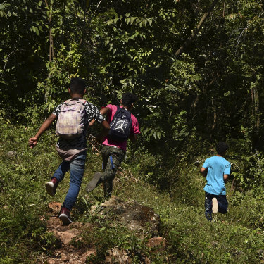 """We're on our way north!"" After eight days on the run from Honduras without food or money, these boys race along a track near the Guatemala-Mexico border."