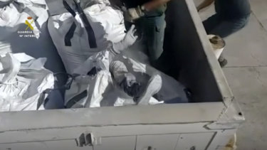 An officer of the Guardia Civil helps a man out from a bag of toxic ashes in a container in Melilla, Spain.