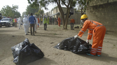 Emergency personnel collect bodies following an attack by suicide bombers at the outskirts of Maiduguri, Nigeria.