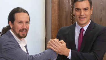 Spain's caretaker Prime Minister Pedro Sanchez, right, and Podemos party leader Pablo Iglesias clasp hands after signing an agreement between the two parties in the Spanish Parliament in Madrid.
