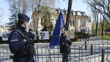 A woman holds a European Union flag outside the Constitutional Tribunal, background in Warsaw.